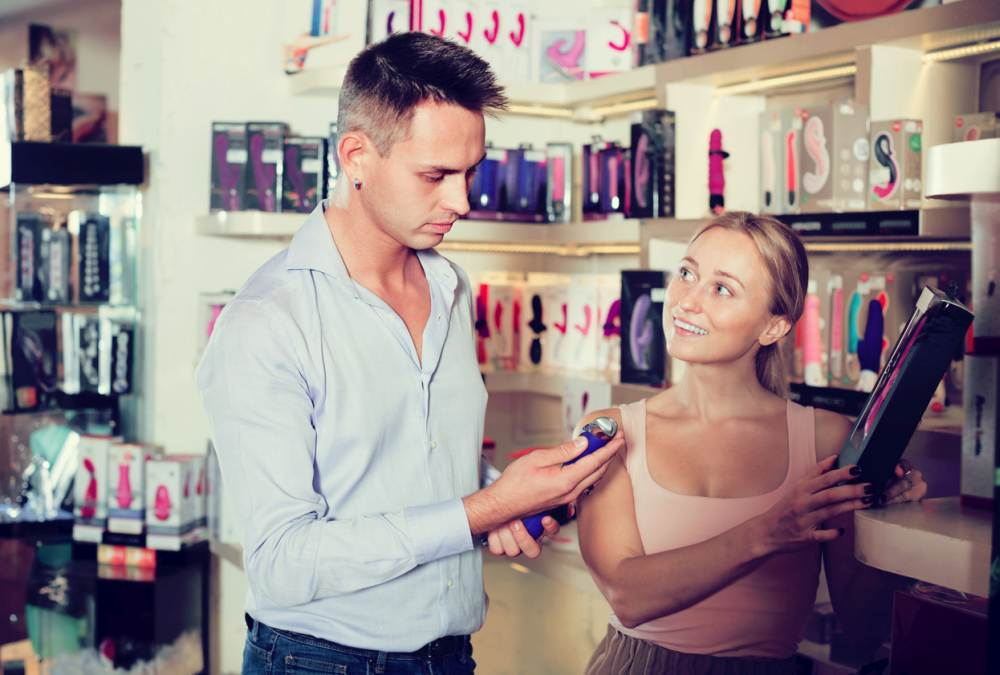Young adult couple buying sex toys in shop