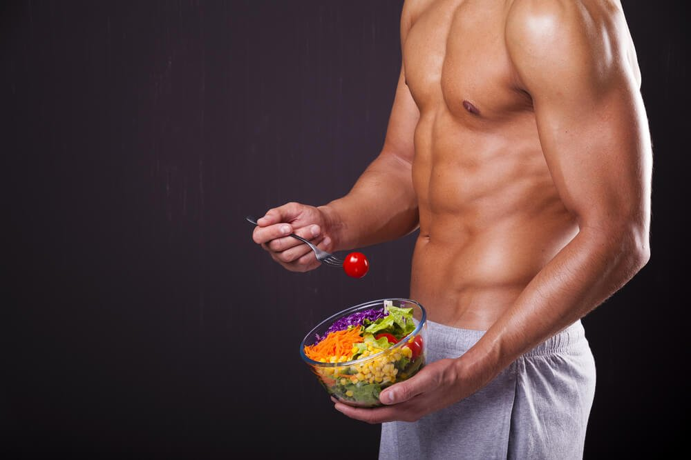 Fit man holding a bowl of fresh salad