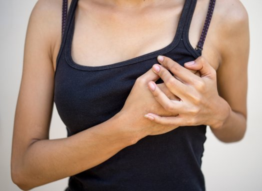 woman with breast pain touching chest